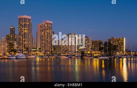 Skyline von Waikiki Bezirk, Honolulu, Hawaii in der Nacht / Dämmerung mit Booten im Hafen Ala Moana und Hilton Hawaiian - Stockfoto