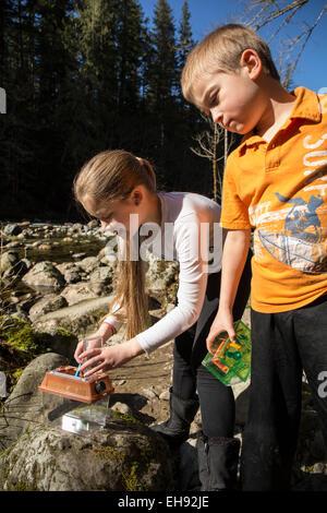 Neunjähriges Mädchen platzieren eine neu Gefangene Insekt in eine Bug Box, während ihrer siebenjährigen Bruder Uhren - Stockfoto