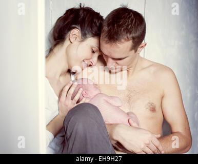 Neue Eltern mit Neugeborenen Baby sitzen - Stockfoto
