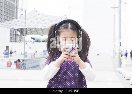 Mädchen Smartphone betrachten und anhören von Kopfhörer im freien - Stockfoto