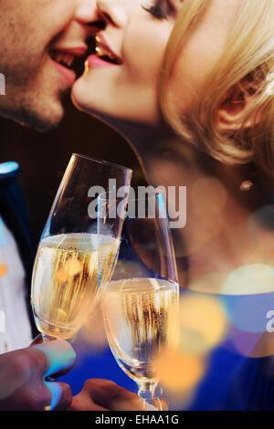 Fröhliches paar küssen und einen Champagner trinken - Stockfoto