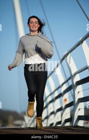 Eine junge 13 14 15 jährige Teenager-Mädchen im freien Laufen Joggen über eine Brücke außerhalb allein selbst UK - Stockfoto