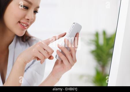 Orientalische junge Frau hält ein Mobiltelefon - Stockfoto