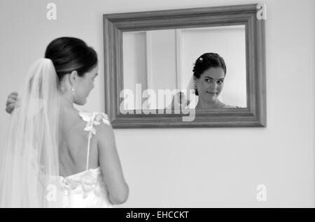 Junge Braut schaut sich im Spiegel an ihrem Hochzeitstag. Frau, Selbstwertgefühl, Selbstbild, Hochzeit und Ehe-Konzept. - Stockfoto