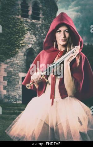 Frau trägt einen roten Umhang mit einem kleinen Schwert