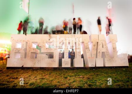 Menschen auf das Bestival Schild am Bestival auf der Isle Of Wight 2011. - Stockfoto