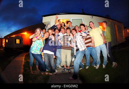 Gruppe der Festivalbesucher mit Wohnwagen am Strand Bombardierung Festival in Newquay. - Stockfoto