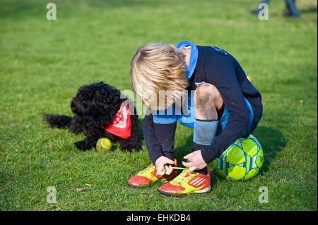 Ein Junge sitzt auf seinem Fußball und sich seine Schnürsenkel auf seine g = Fußballschuhe während seinem Hund sitzt - Stockfoto