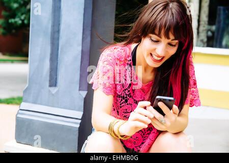 Kaukasische Frau mit Handy auf Bürgersteig - Stockfoto