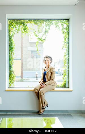 Gemischte Rassen Geschäftsfrau lächelnd in Bürofenster Stockfoto