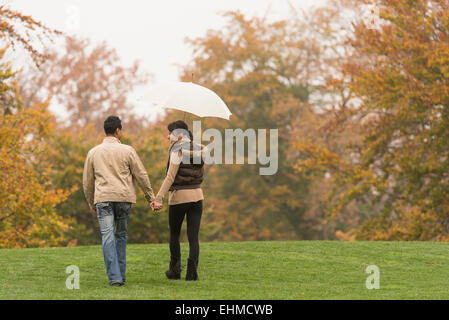 Paare, die mit Regenschirm im park - Stockfoto