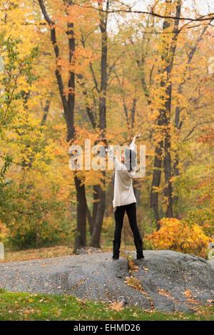 Asiatische Frau jubeln mit ausgestreckten auf Felsen im park - Stockfoto