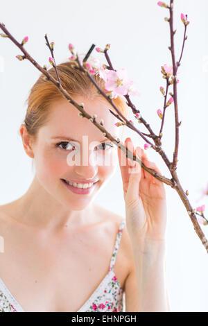 Frau vor einem Blooning Prunus Zweig. - Stockfoto