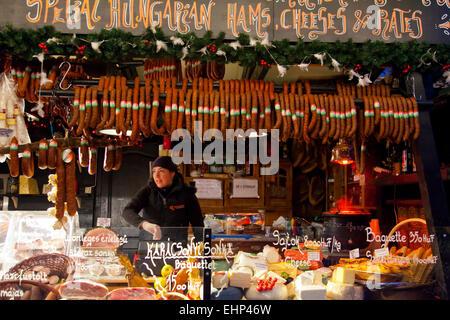 Eine Mädchen verkauft, Fleisch und Käse auf einem Weihnachtsmarkt in Budapest, Ungarn - Stockfoto