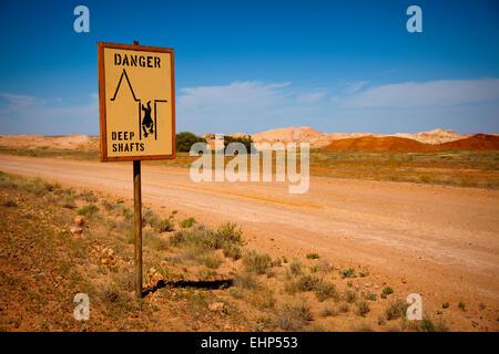 Ein Verkehrszeichen Warnung vor tiefen Minenschächte in Opal Bergbau Land, Coober Pedy, Australien - Stockfoto