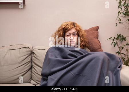 Müde rothaarige Frau, die eine Erkältung und ruht auf dem Sofa zu Hause. - Stockfoto