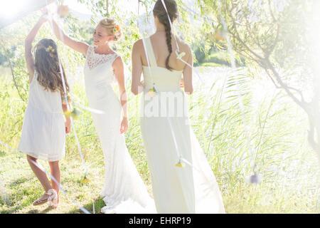 Braut und Brautjungfer spielen mit Dekorationen im Hausgarten während der Hochzeitsfeier - Stockfoto
