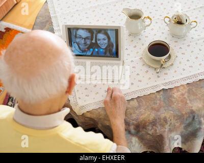 Großvater Videokonferenzen mit Enkel über digital-Tablette - Stockfoto