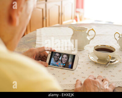 Großvater Videokonferenzen mit Enkelkindern per smartphone - Stockfoto