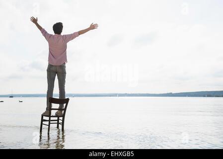 Junger Mann stehend Stuhl See allein Sonnenuntergang - Stockfoto