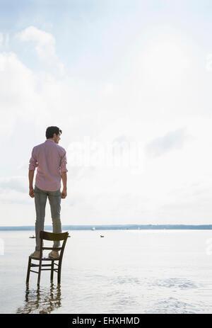 Junger Mann stehend Stuhl See allein nachdenklich - Stockfoto
