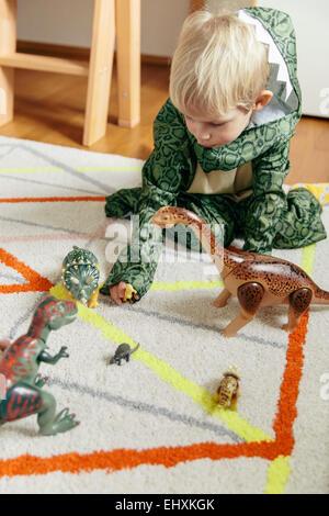 Kleiner junge Dinosaurier Kostüm spielen mit Spielzeug Dinosaurier - Stockfoto