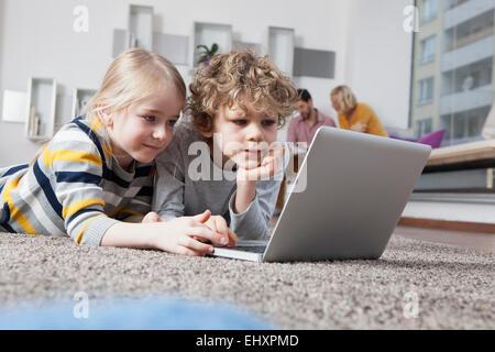 Bruder und Schwester auf Boden mit laptop - Stockfoto