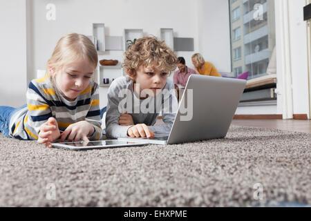 Bruder und Schwester auf Boden mit Laptop und digital-Tablette - Stockfoto