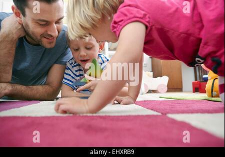 Vater und Kinder mit Mini-Tablet am Boden liegend - Stockfoto