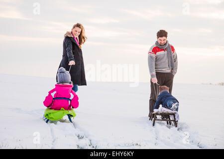 Glückliche Familie im Schnee Rodeln - Stockfoto