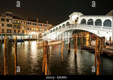 Pier mit Boot am Canal Grande bei der Rialto-Brücke in der Nacht. - Stockfoto