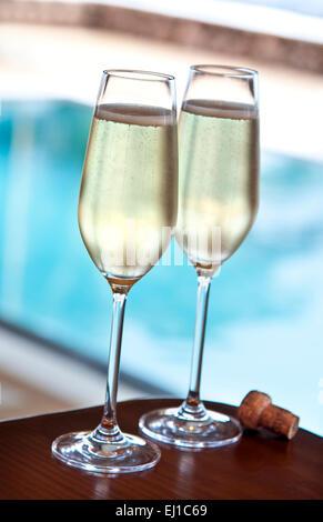Champagner POOL LUXUS Zwei frisch Gläser Champagner und Kork auf Alfresco Terrasse Tisch mit luxuriösen Infinity - Stockfoto