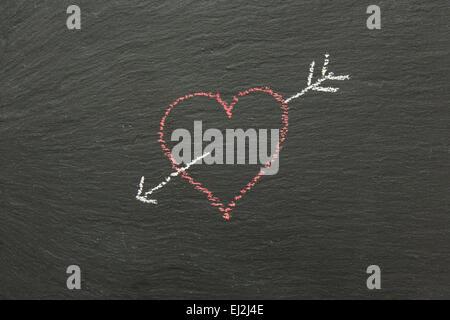 Kreide-Herz mit Pfeil auf einer Tafel gezeichnet... - Stockfoto