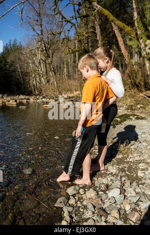 Sieben Jahre alter Junge und seine neunjährige Schwester behutsam die Kälte der Snoqualmie River, mit ihren Zehen - Stockfoto