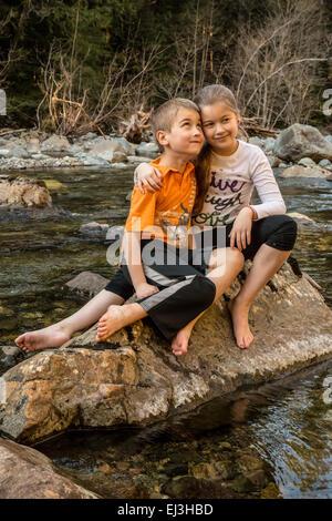 Neunjähriges Mädchen gab ihr sieben Jahre alten Bruder eine Umarmung beim Sitzen auf einem Felsen in einem seichten - Stockfoto