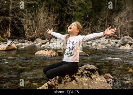 Neun Jahre altes Mädchen mit Begeisterung und Freude warf ihre Arme breit, in Snoqualmie River in North Bend, Washington - Stockfoto
