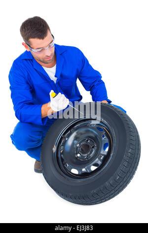 Mechaniker arbeiten an Reifen auf weißem Hintergrund - Stockfoto