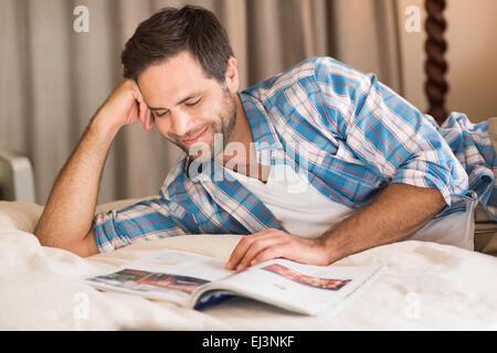 Entspannen Sie sich auf seinem Bett lesen Magazin schöner Mann - Stockfoto