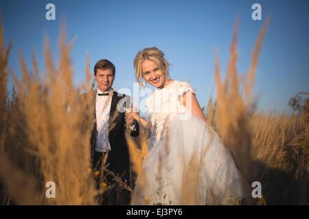 Jung, elegant gekleidet paar Hochzeit geht auf ein Feld mit hohen e - Stockfoto