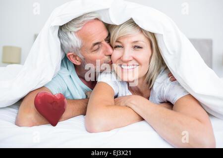 Zusammengesetztes Bild Nahaufnahme von reifer Mann küssen Womans Wange im Bett - Stockfoto