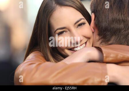 Porträt einer glücklichen Freundin ihrem Freund umarmt und Blick in die Kamera - Stockfoto