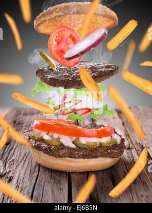Pommes Frites mit Burger in frieren Bewegung isoliert auf weiss - Stockfoto