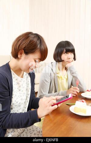 Junge japanische Mädchen mit einem Stück Kuchen zusammen im Wohnzimmer - Stockfoto
