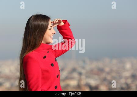 Frau freut sich im Winter mit einem roten Mantel mit Stadt im Hintergrund - Stockfoto
