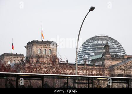 Berlin, Deutschland. 25. März 2015. Ein Bus fährt von Deutsche nationalen Flaggen auf Halbmast auf das Reichstagsgebäude - Stockfoto