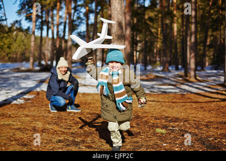 Kleiner Junge mit Spielzeug Flugzeug und seinem Vater blickte ihn laufen - Stockfoto