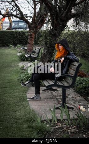 Frau mit leuchtend orangen Haaren saß auf einer Parkbank in einem Stadtpark in Hampshire, UK mit Kapuze, mit Tulpen - Stockfoto