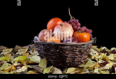 Alte korb Schale mit Herbst Früchte über schwarzen Hintergrund isoliert. Fläche voller trockene Blätter - Stockfoto