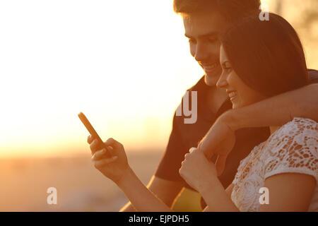 Brautpaar mit einem Smartphone in einem Sonnenuntergang zurück Licht am Strand - Stockfoto