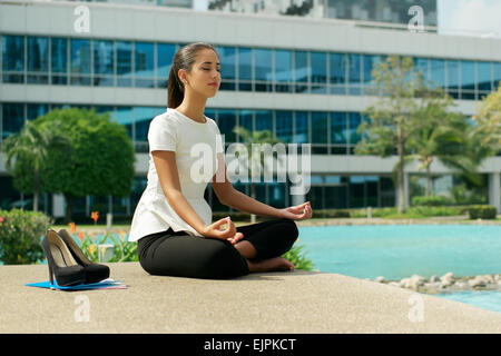 Jung betonte Hispanic Business-Frau beim Yoga vor Bürogebäude, sitzen im Lotussitz mit auf Knien in Händen der - Stockfoto